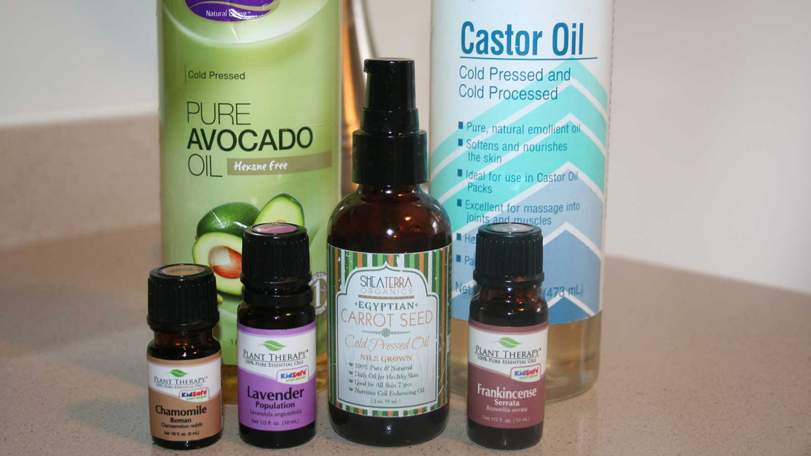 Ingredients for the oil cleansing method, including avocado oil, castor oil, carrot seed oil and plant therapy essential oils.