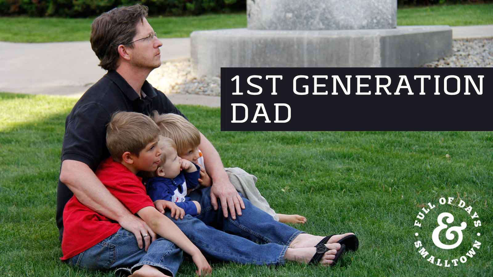 Father and Sons Sitting Together on a Grass Lawn Header