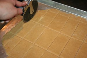 Cutting homemade Graham crackers with a pizza cutter.