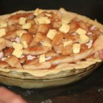 Dotting the pear pie with butter before baking