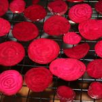 Sliced beets on a dehydrator tray ready to be made into homemade beet chips