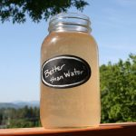 Better Than Water in a quart mason jar sitting on the rail of a deck with blue sky and green trees in the background.