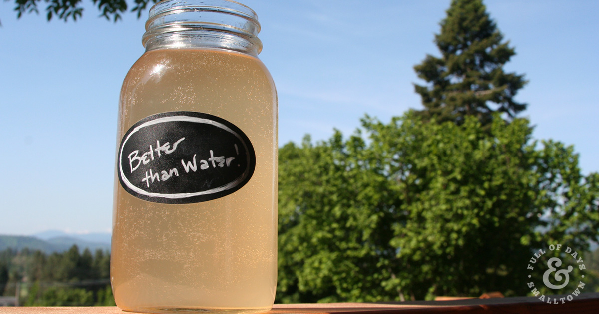 Better Than Water in a quart mason jar, sitting on deck railing with blue sky and green trees in the background.
