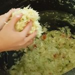 Squeezing and pressing the sauerkraut to release the juices.