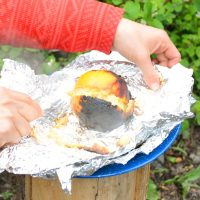 Sourdough Orange Cake just out of the fire. Cake batter is in the orange peel, then wrapped in tinfoil.