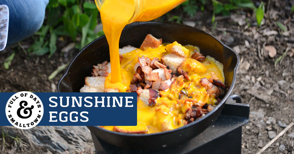 Sunshine Eggs Camping Breakfast, image shows eggs being poured into a cast iron pan with bacon and bread cubes.