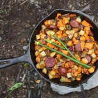 Sweet potato hash in a cast iron skillet on a rocket stove.