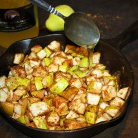 Pears with spices in cast iron pan being drizzled with honey