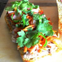 Chicken Banh Mi with pickled radishes and carrots, topped with cilantro and sliced jalapenos on a ciabatta roll.,