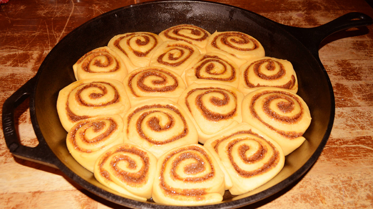 Sourdough Sweet Potato Cinnamon Rolls risen in a cast iron skillet, ready to bake.