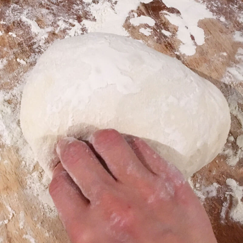 Carefully flip dough over so the seam side is down and smooth any edges that need to be re-shaped into a ball.