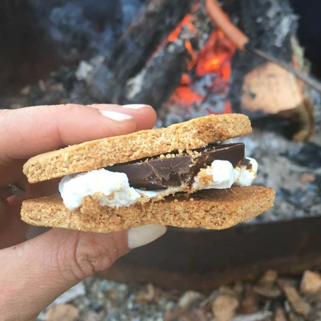 Homemade S'more with a campfire in the background.