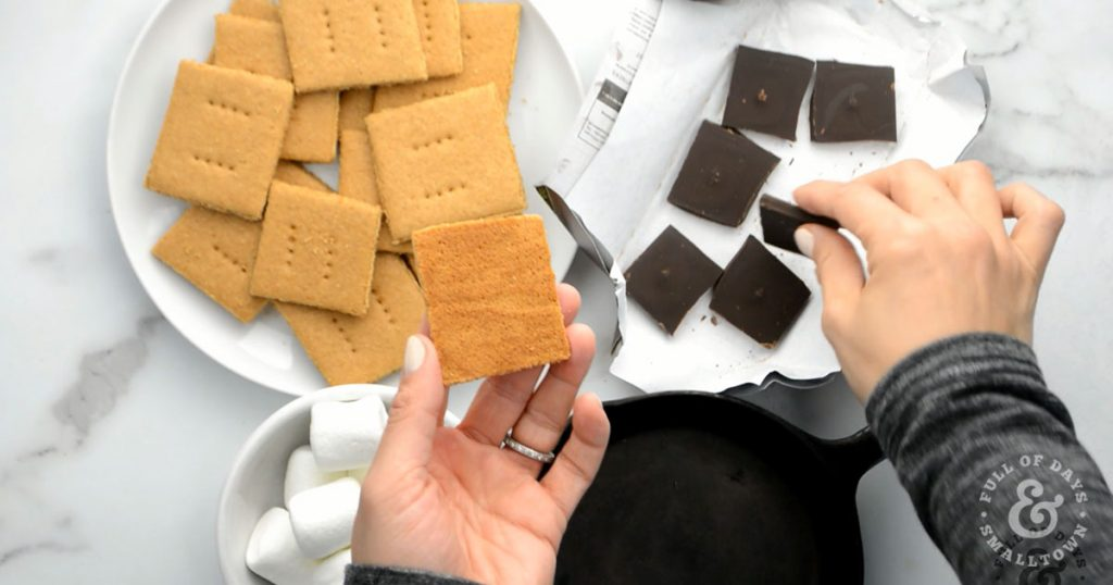 Homemade Graham Crackers, chocolate squares and marshmallows being put together for the perfect s'more.