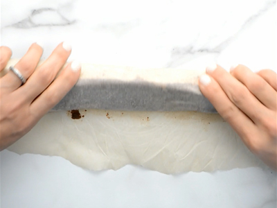 Wrapping chocolate cookie dough in parchment paper and forming into a long round log for healthy homemade oreos.