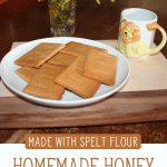 "Image of a white plate with a pile of homemade graham crackers. Text overlay says, ""Homemade Honey Graham Crackers Made with Spelt Flour""."